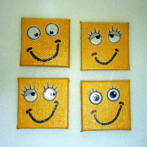 Vier gelbe lachende Smiley Magnete