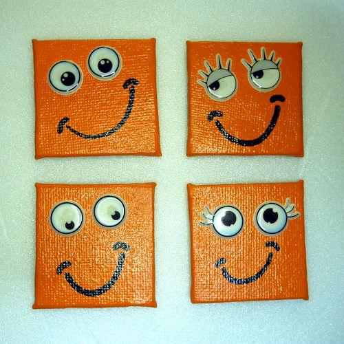Vier orange lachende Smiley Magnete