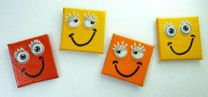 Vier lachende Smiley Magnete in den Farben rot, gelb und orange