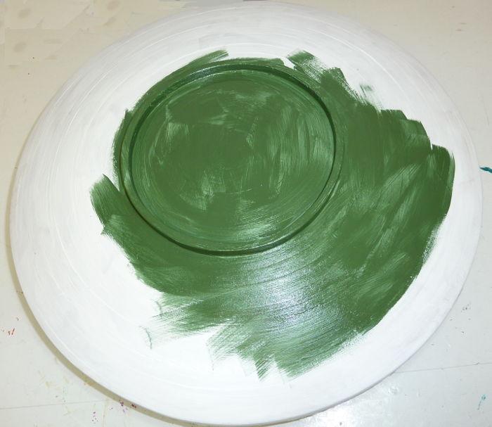 Holzschale von unten beim Bemalen mit Acrylfarbe in grün