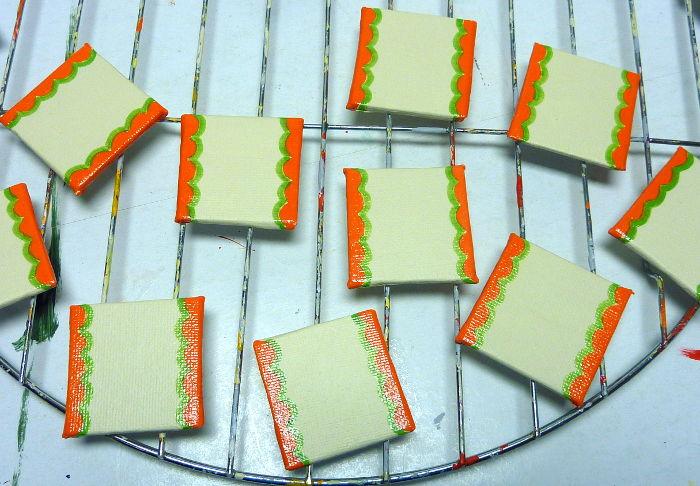 Bemalte Malkartons liegen zum Trocknen auf dem Gitter