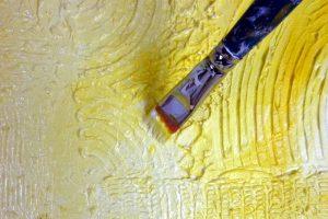 Großansicht Pinsel beim Bemalen der strukturierten Oberfläche mit Acrylfarbe